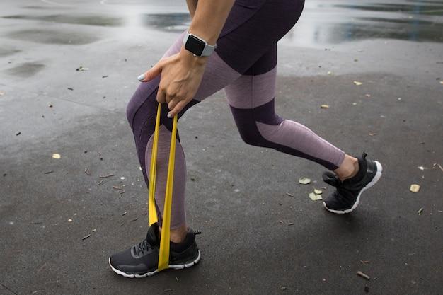 Спортсменка тренируется с желтой эластичной веревкой на спортивных площадках в парке
