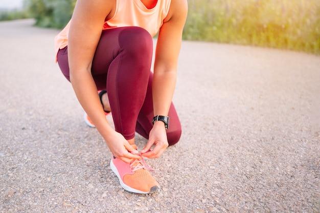 トレーニングの前に靴ひもを結ぶスポーツウーマン。