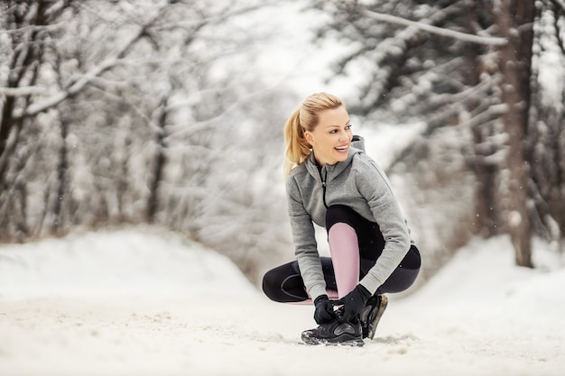 Sportswoman tying shoelace while kneeling on snowy path at winter day.