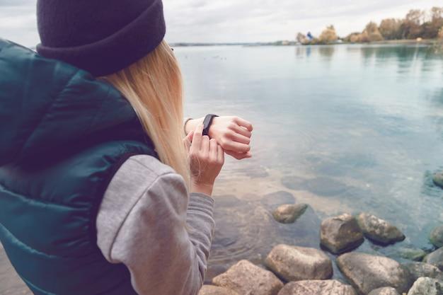 Sportswoman uses an electronic bracelet-pedometer standing on the lake shore.