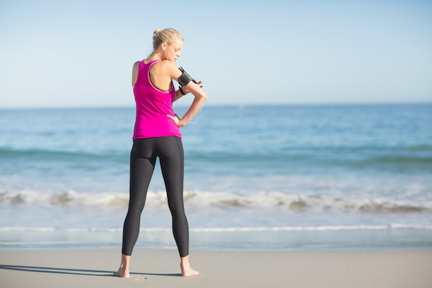 Sportswoman using mobile phone on beach