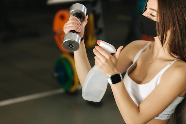 Спортсменка в защитной маске дезинфицирует руки и гантели в тренажерном зале.
