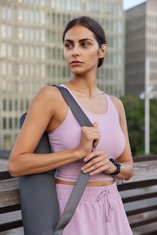 スポーツウーマンはタンクトップを着用し、ショーツはヨガマットを運び、ピラティストレーニングの準備をします。都市のスクレーパーで健康的なライフスタイルのポーズを考えます