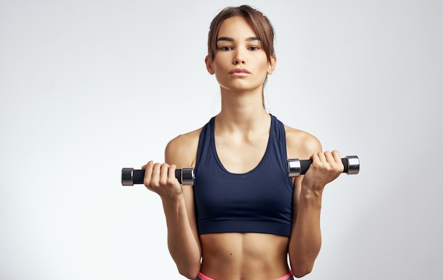 Sportswoman with dumbbells on a light background gesturing with her hands fitness model