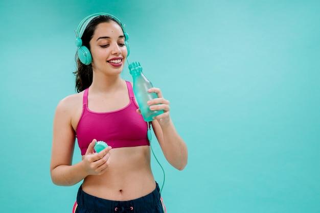 Sportswoman with earphones drinking water