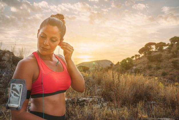 Sportswoman con auricolari nella natura