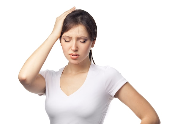 A sportswoman with a headache holding head on white background