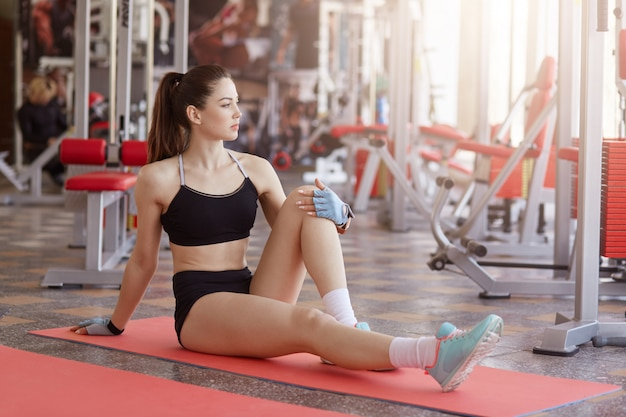Sportswoman with long beautiful legs doing stretching exercise. fit woman exercising in gym, wearing top and short, has ponytail, looking aside, looks confident.