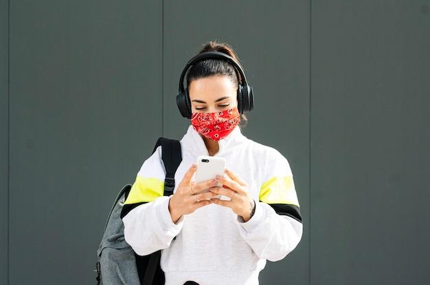 ヘッドフォンとスマートフォンで音楽を聴くマスクを持つスポーツ選手