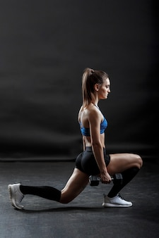 A sportswoman with ponytail hairstyle is doing fitness exercise