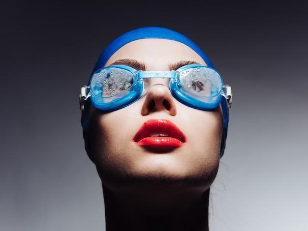 青い水泳帽とメガネで赤い唇がトリミングされたビューを見上げているスポーツウーマン。高品質の写真