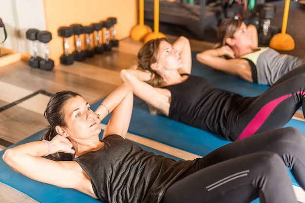 Sportswomen doing abs exercise in gym. concept of gym.