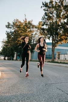 Sportswomen running on street in sunlight