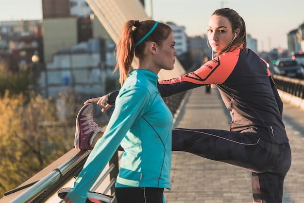 Sportswomen stretching legs