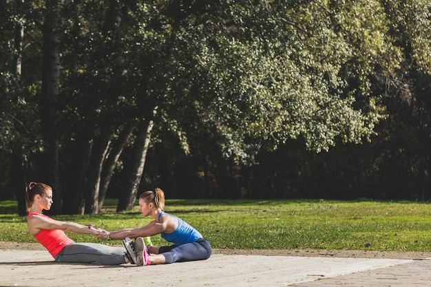 Sportswomen stretching together outdoors