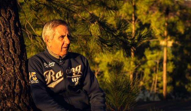 Красивый старший мужчина с sportwear отдыхает на дереве в лесу и смотрит вдаль