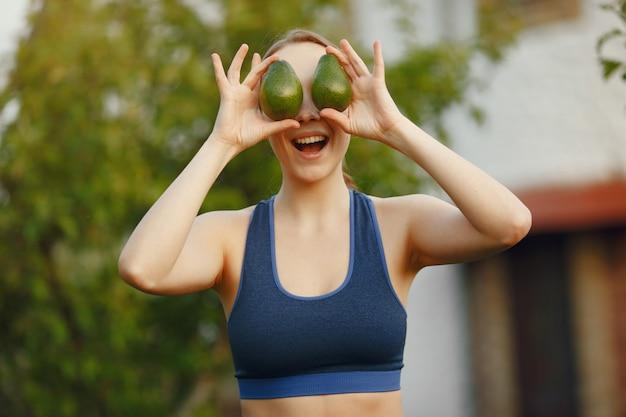 Sportwearの女性は果物を保持します