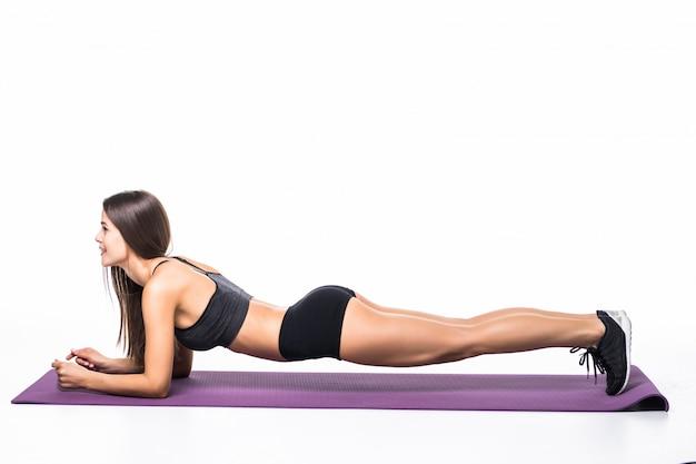 Красивая девушка фитнеса в sportwear работая делающ доску на белизне