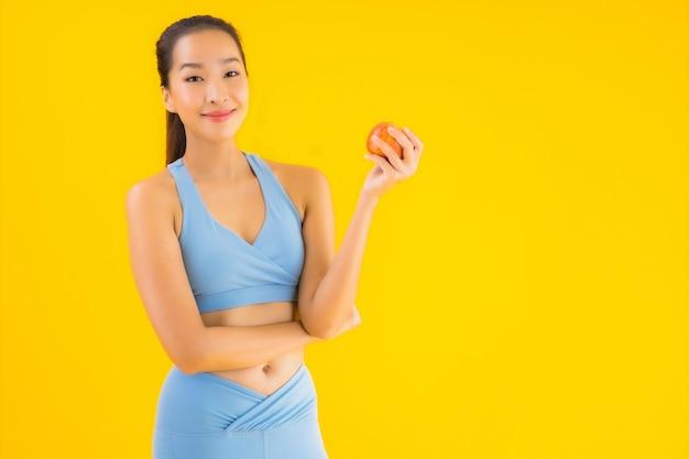 Sportwear носки женщины портрета красивый молодой азиатский готовый для тренировки на желтом цвете