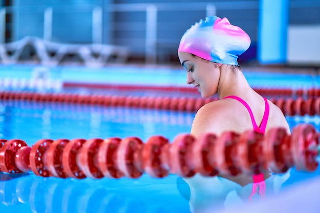 Sporty active fit female swimming in sports pool in leisure center.