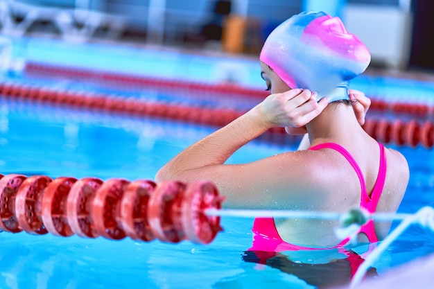 Sporty active fit woman swimming in sports pool in leisure center.