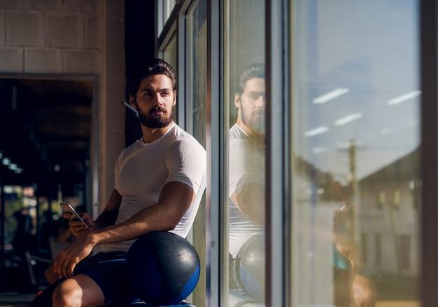 Спортивный активный мужчина сидит у окна в тренажерном зале с мобильным телефоном в руке и большим мячом рядом с ним и смотрит вдаль.