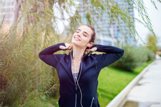 Sporty and active woman runner is listening to music