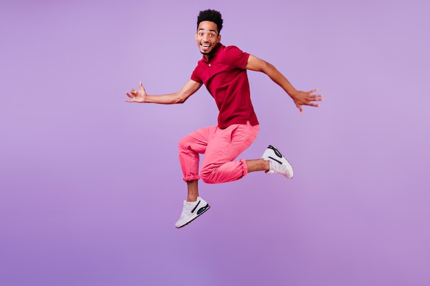 リラックスできる赤いカジュアルなtシャツを着たスポーティなアフリカ人。短い黒髪がジャンプするポジティブな男性モデル。