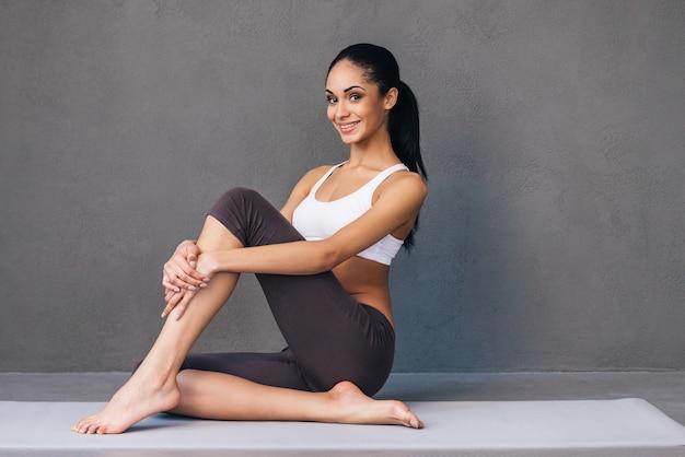 Спортивная и подтянутая красота. красивая молодая африканская женщина в спортивной одежде смотрит в камеру с улыбкой, сидя на коврике для упражнений на сером фоне