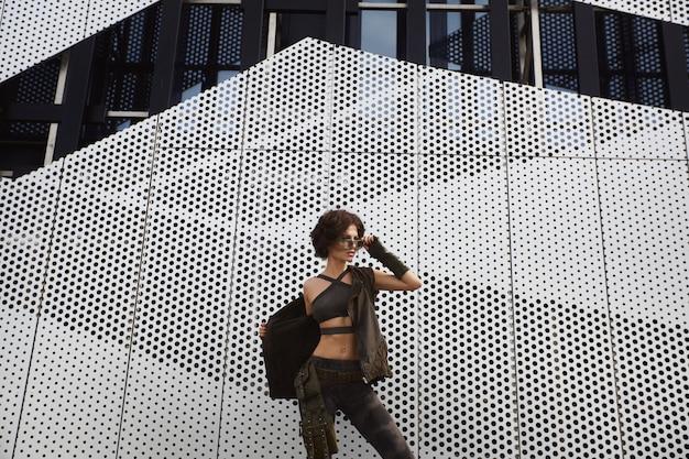 Спортивная и сексуальная брюнетка-фитнес-девушка с идеальным телом в стильных солнечных очках и военном костюме снимает жилет и позирует на улице в городе