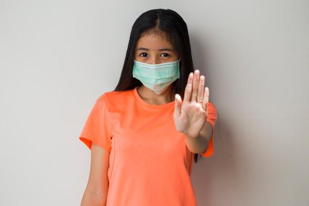 보호 covid-19 흰색 배경에 포즈 의료 마스크를 쓰고 스포티 한 아시아 소녀