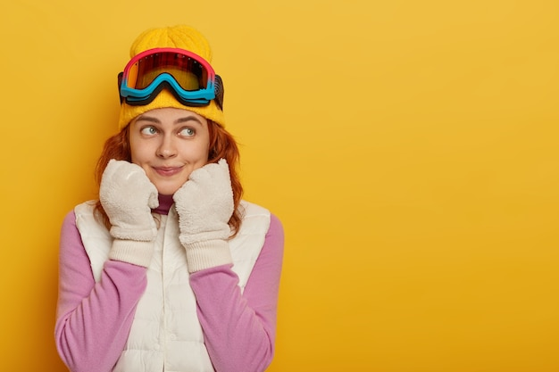 Sporty athletic girl skier looks pensively aside, wears white winter gloves and vest, snowboarding goggles, looks aside, poses against yellow studio wall, blank space