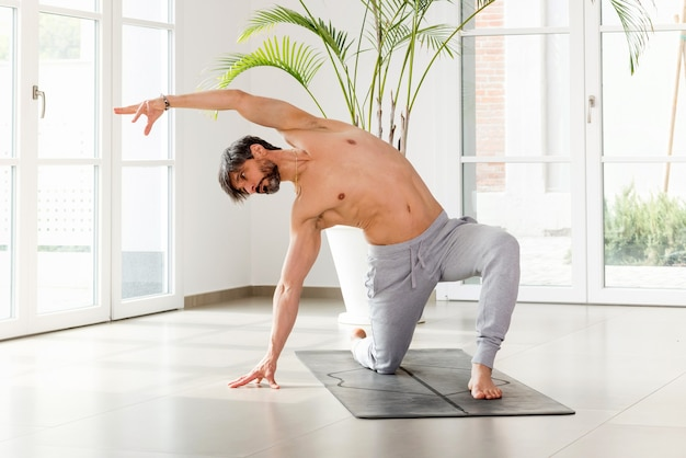 Sporty athletic man doing yoga mobility exercises with a forward lunge side stretch to strengthen and tone his muscles in a high key gym with copyspace in a health and fitness concept