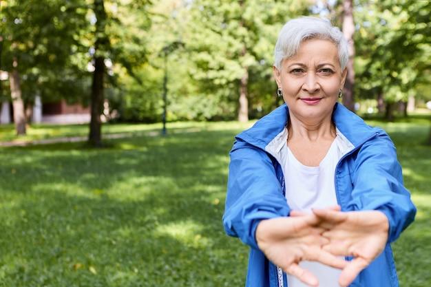 スタイリッシュなウェアを身に着けたスポーティなアスレチック引退した女性は、屋外で手の筋肉を伸ばし、ヨガの練習をし、体調を整えます。うれしそうな成熟した女性年金受給者が腕を伸ばして