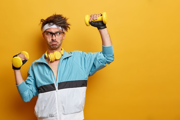 Sporty athletic strong man lifts dumbbells and works hard on training biceps, leads active healthy lifestyle, has regular physical exercises, poses against yellow wall, empty space aside