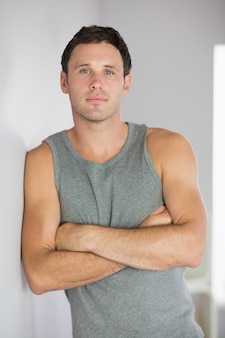 Sporty attractive man leaning against wall with arms crossed