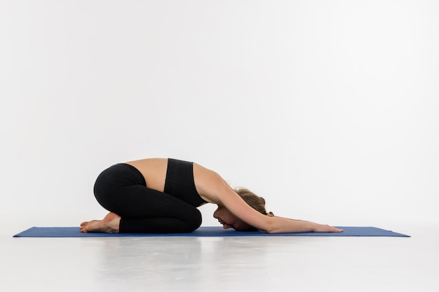 Sporty привлекательная молодая женщина делая практику йоги на белой предпосылке. детская поза, баласана.