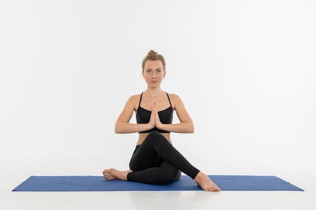 Sporty привлекательная молодая женщина делая практику йоги на белой предпосылке. gomukhasana