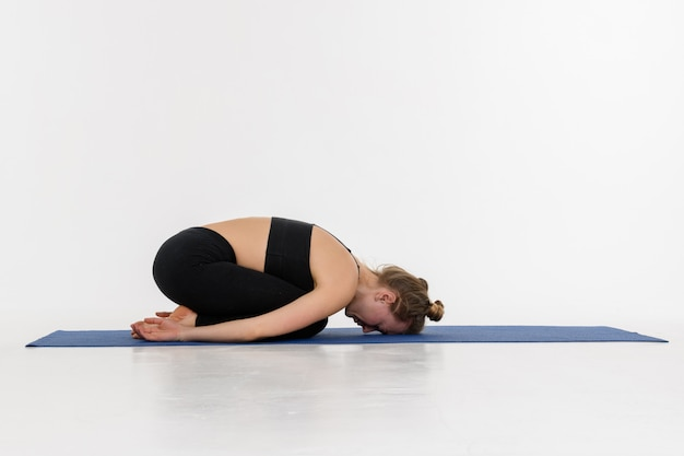 Sporty attractive young woman doing yoga practice on white background. child's pose, balasana.
