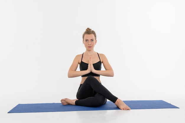 Sporty attractive young woman doing yoga practice on white background. gomukhasana