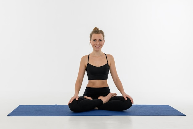 Sporty attractive young woman doing yoga practice on white background. sukhasana.
