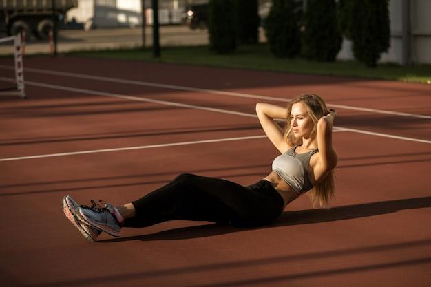 Спортивная красивая блондинка делает приседания на животе на теннисном корте