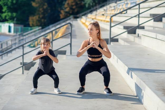 屋外でフィットネストレーニング中に一緒にしゃがむスポーティな美しい姉と妹。