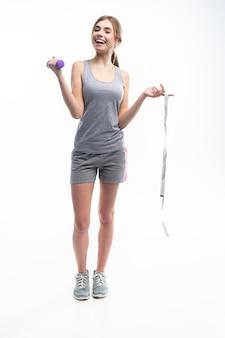 Спортивная красивая женщина тренируется с гантелями, показывает это на камеру и держит в руке измерительную ленту.