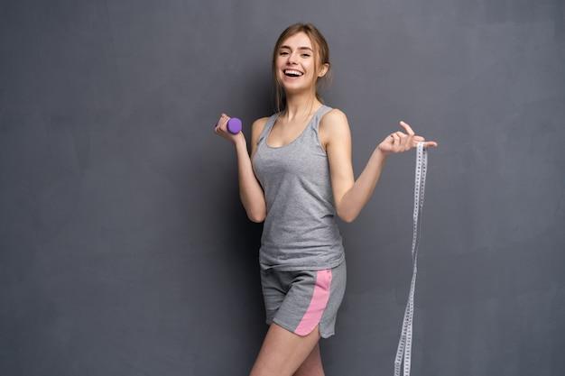 아령으로 운동 스포티 한 아름 다운 여자, 카메라에 그것을 보여주고 그녀의 손에 측정 테이프를 보유