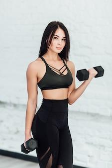 Спортивная красивая женщина тренируется с гантелями дома, чтобы оставаться в форме