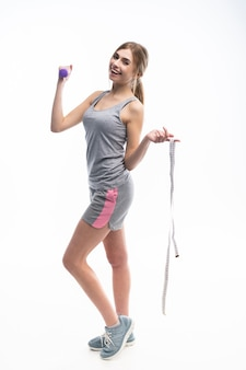 Sporty beautiful woman exercising with a dumbbell, shows it to the camera and holds a measuring tape in her hand.
