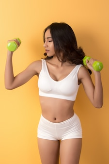 Sporty beautiful woman exercising with dumbbell