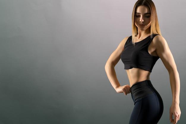Sporty beautiful woman on grey