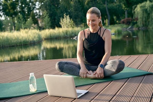 Sporty beautiful woman looking happy watching tutorial on a laptop while doing yoga on a mat in